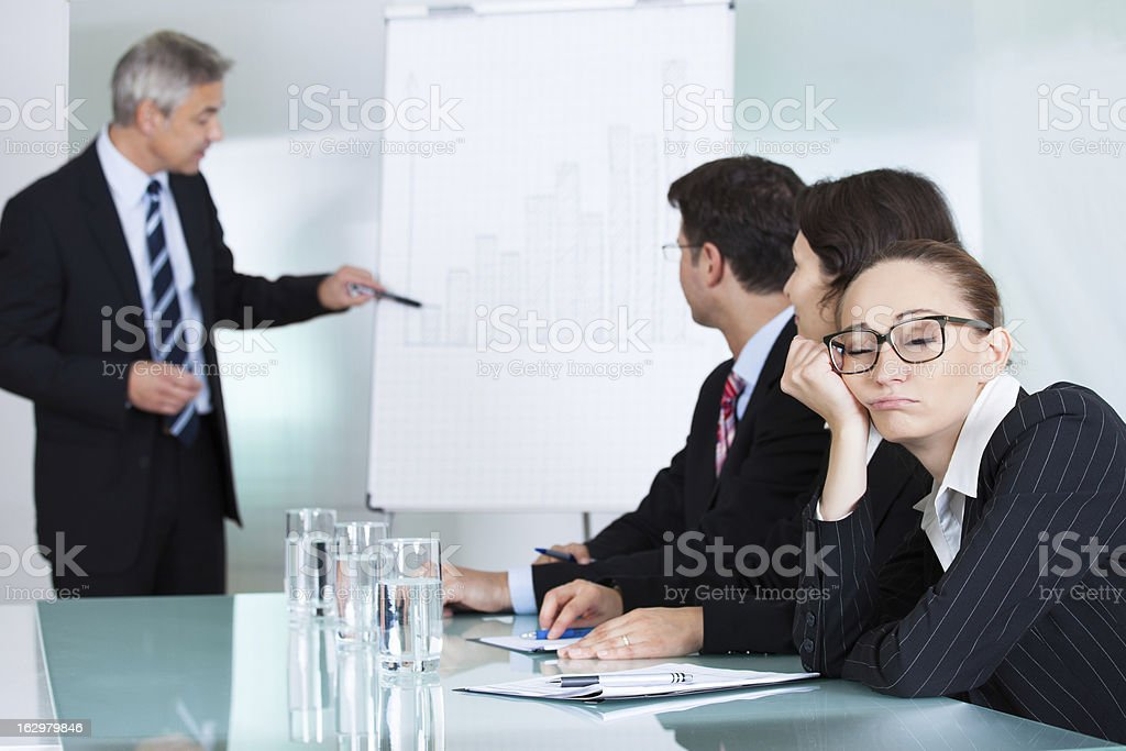 Bored businesswoman sleeping in a meeting stock photo