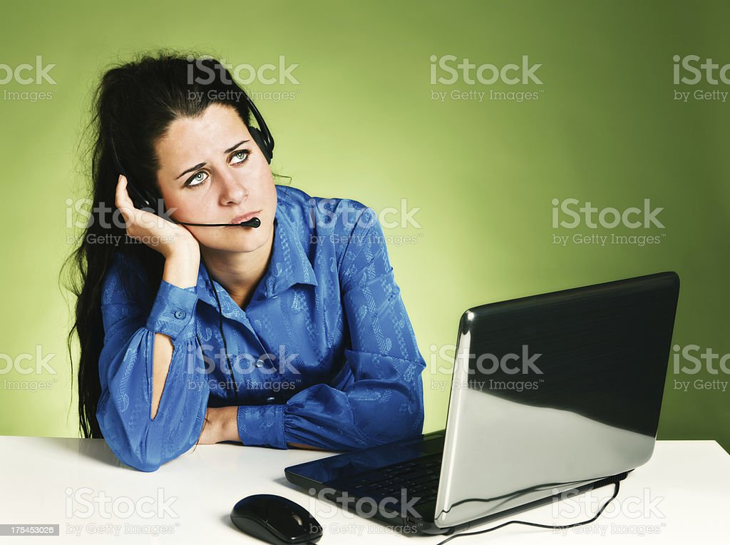 Bored call center employee in headset rolls eyes royalty-free stock photo