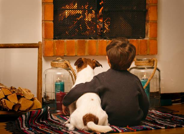 Bored kind en hond die thuis tijdens quarantaine lettend op brand in open haard blijven foto