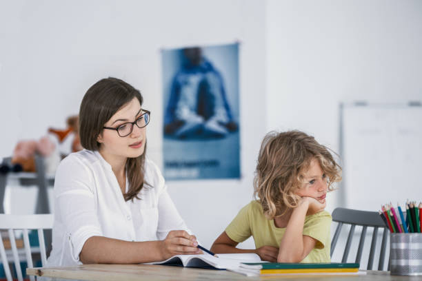 A bored child refusing to cooperate with his private teacher while doing homework. stock photo