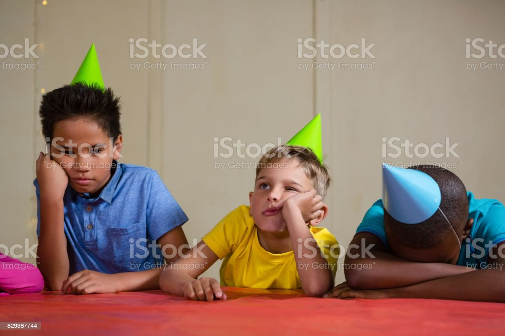 Bored children wearing party hat at table stock photo