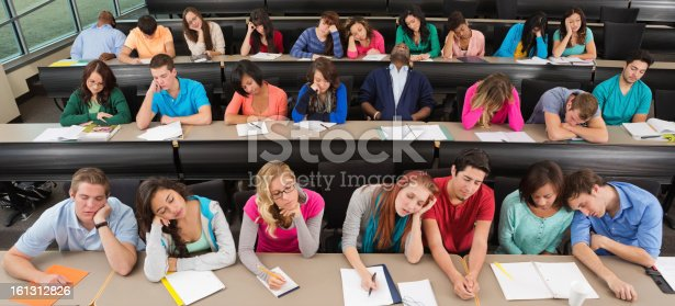istock Bored college students asleep on desks in lecture hall classroom 161312826