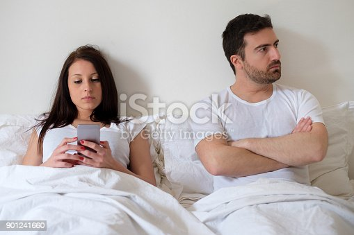 660634310 istock photo Bored couple and worried man by his wife internet addiction 901241660