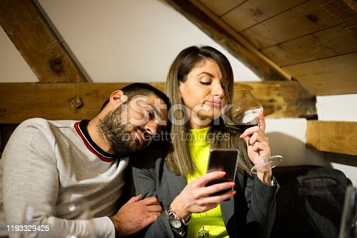 660639880 istock photo Bored couple and worried man by his wife smart phone addiction 1193329425