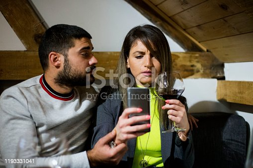660639880 istock photo Bored couple and worried man by his wife smart phone addiction 1193331041