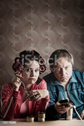 One middle aged couple eating dinner in front of tv. More files of this series and models on port. Made with professional make up and studio equipment. Vertical format.