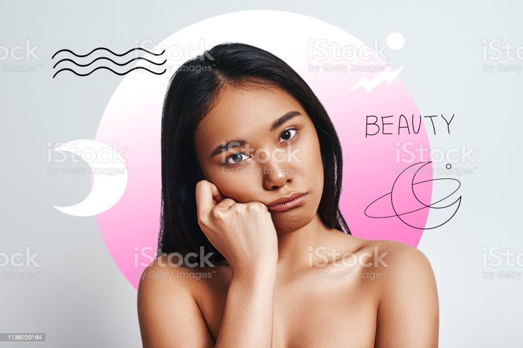 Bored. Cute young asian woman looking at camera and making a sad face...
