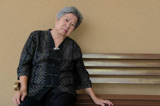 Langweilig depressive ältere Frau auf Bank sitzen. Ältere Frauen fühlen sich traurig einsam – Foto
