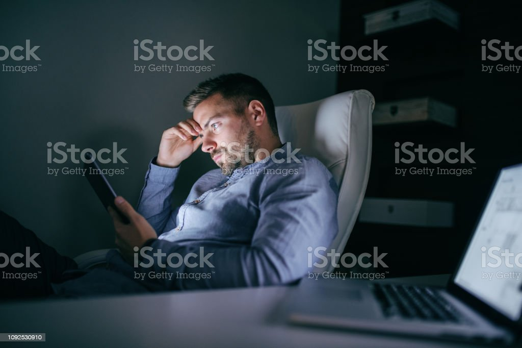 Bored employee sitting in the office late at night and using tablet. Side view. - Royalty-free Adult Stock Photo