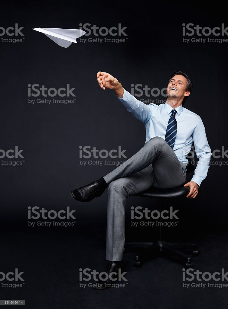 Bored executive throwing paper airplane stock photo