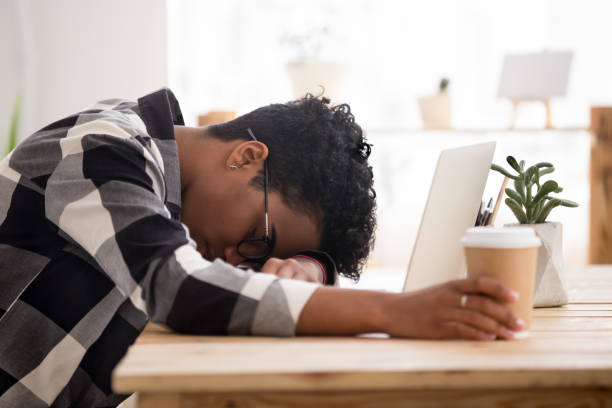 bored exhausted african american woman falling asleep sleeping at workplace - sleeping in work stock photos and pictures