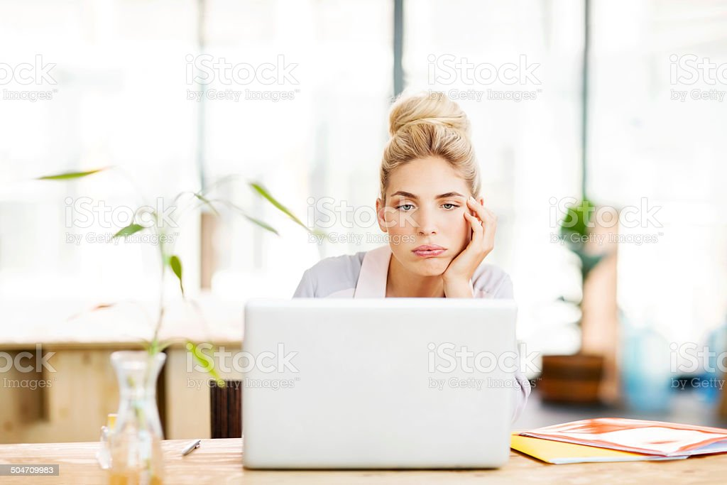 Bored Female Entrepreneur Using Laptop At Desk stock photo