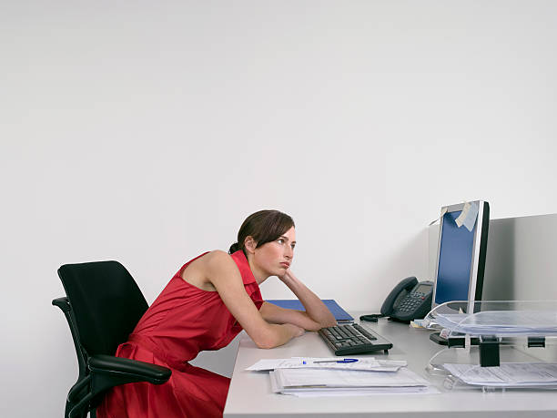 Bored Female Office Worker At Desk Side view of a bored female office worker looking at notes on computer monitor at desk bad posture stock pictures, royalty-free photos & images