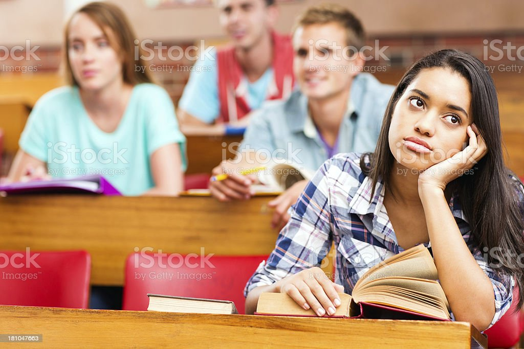 Bored Female Student With Book Sitting At Desk royalty-free stock photo