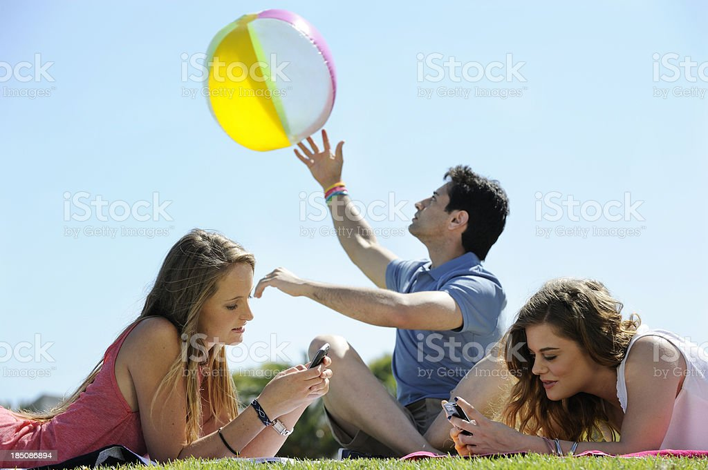 Bored friend plays ball while girls text away stock photo