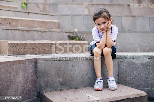 istock bored girl alone in school yard 1172766507