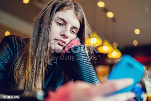 Teenage girl in cafe text messaging on smartphone