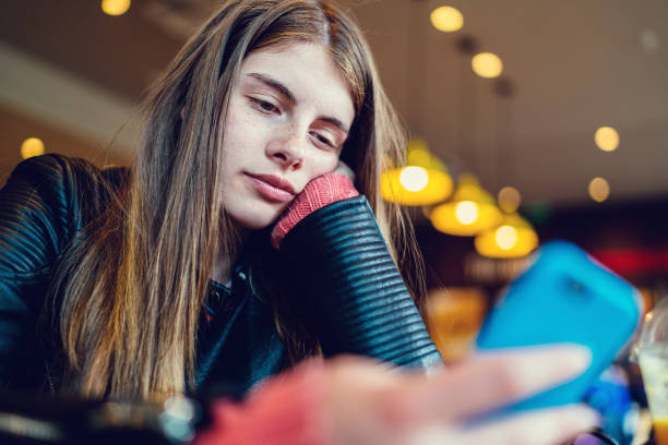 Bored girl in cafe texting stock photo