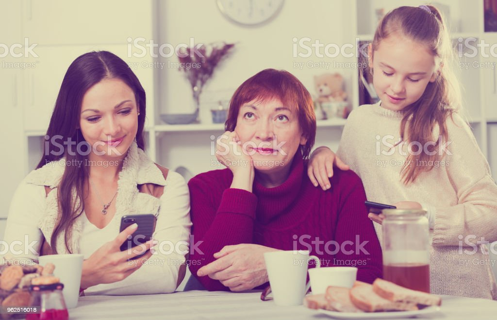 Vovó entediada com a filha e a neta olhando para telefones - Foto de stock de 25-30 Anos royalty-free