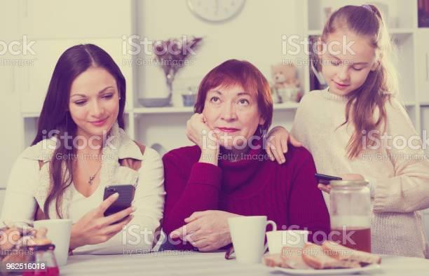 Foto de Vovó Entediada Com A Filha E A Neta Olhando Para Telefones e mais fotos de stock de 25-30 Anos