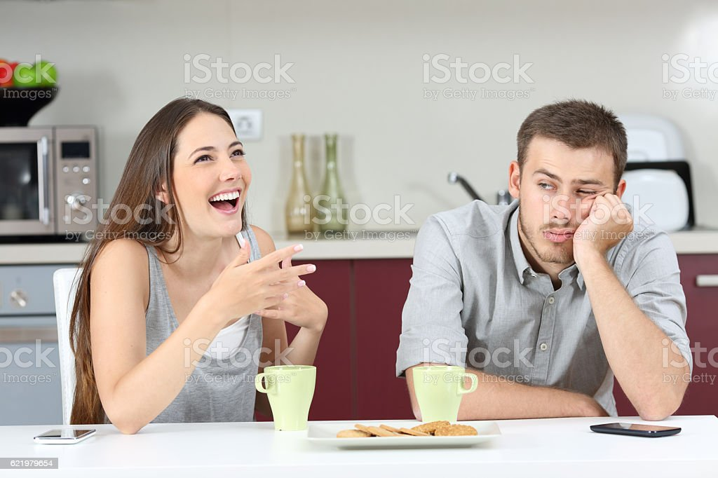 Bored husband hearing his wife talking stock photo