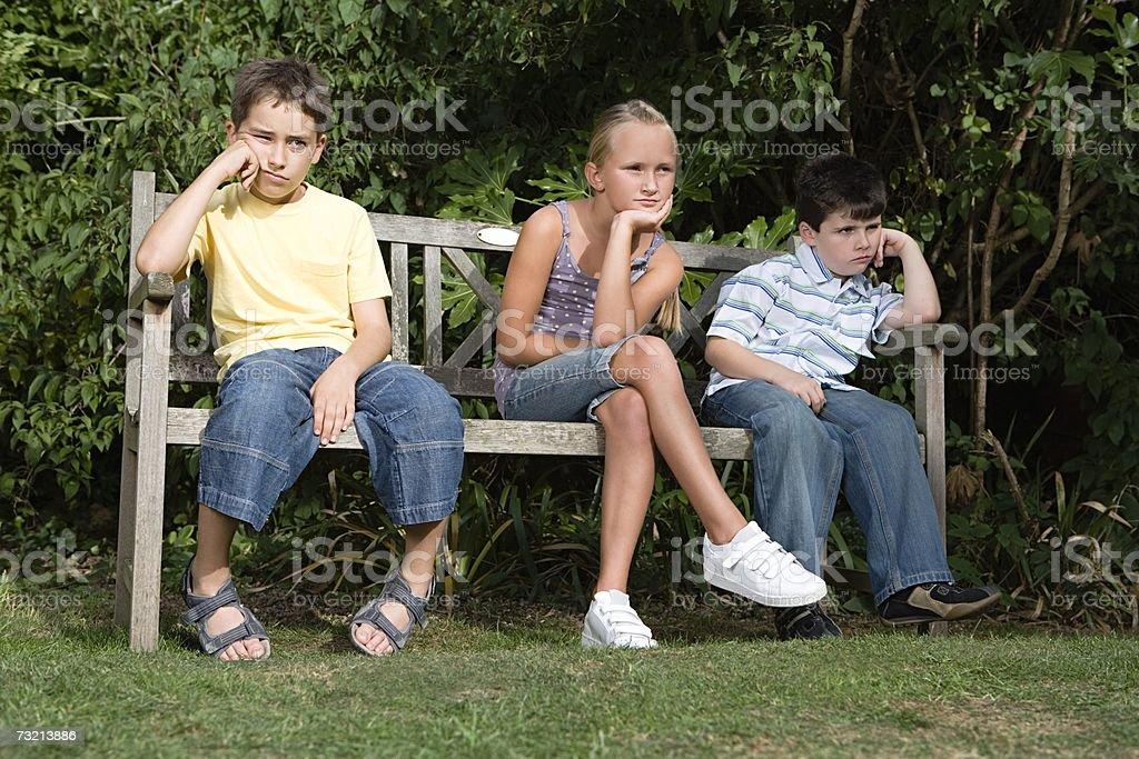 Aborrecido crianças em um Banco de Parque foto de stock royalty-free