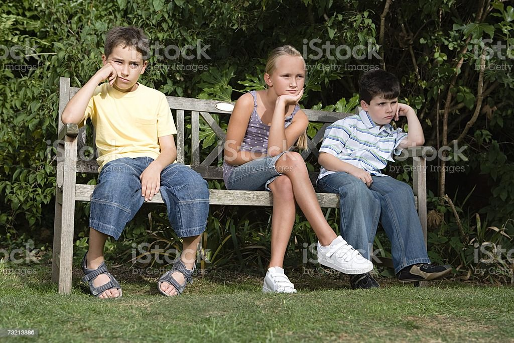 Bored kids on a park bench stock photo