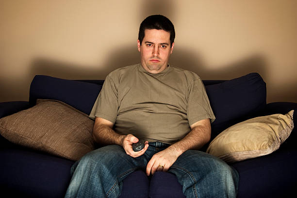 bored, lazy, overweight man sits on the sofa - sloth stock pictures, royalty-free photos & images
