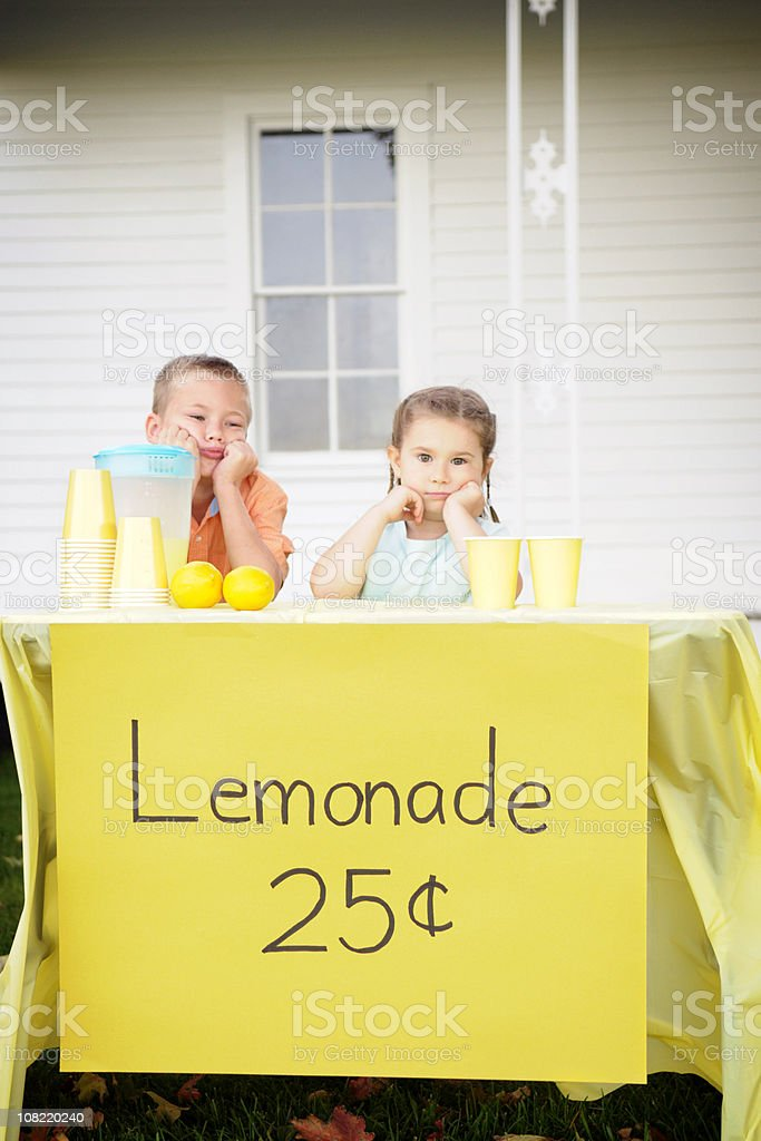 Bored Little Boy and Girl Sitting at Lemonade Stand royalty-free stock photo