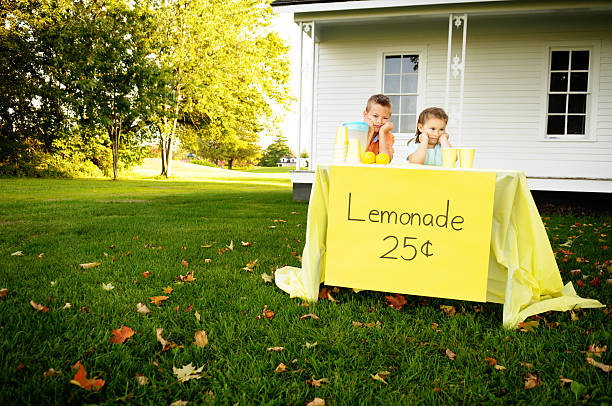 Bored Little Boy and Girl Standing Behind Lemonade Stand A young boy and girl stand bored behind their lemonade stand. lemonade stand stock pictures, royalty-free photos & images