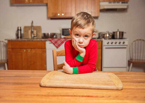 bored little boy sitting in the kitchen at the table stock photo