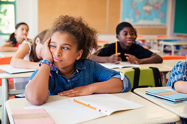 Bored little girl in elementary classroom. stock photo