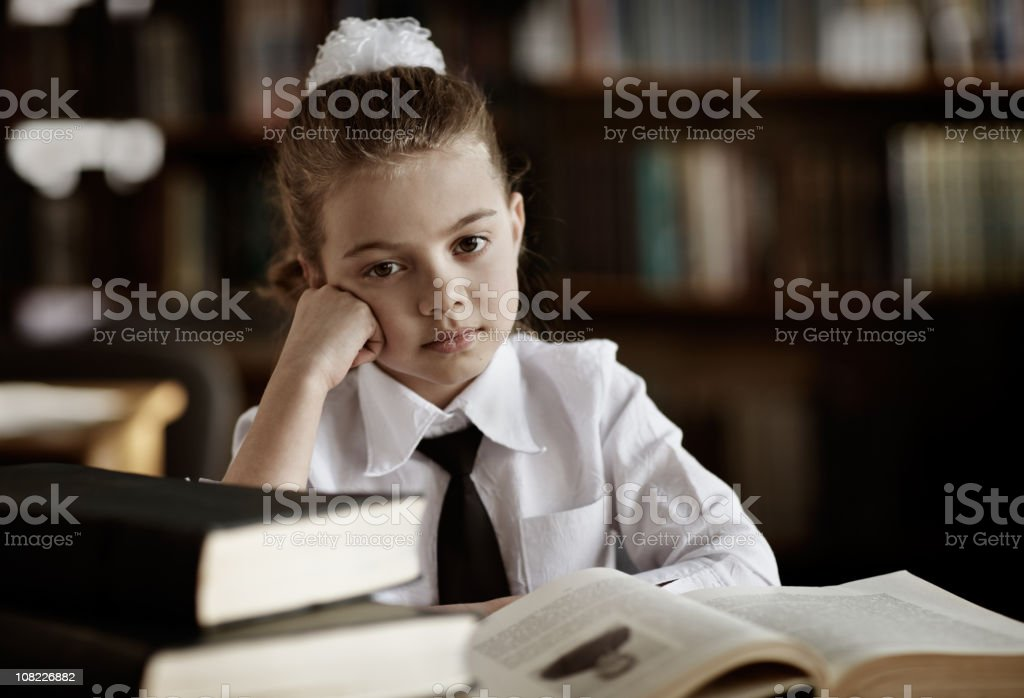 Bored Little Girl Wearing School Uniform in Library royalty-free stock photo