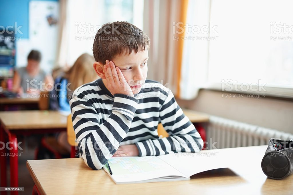 Bored little school boy in classroom looking out of window stock photo