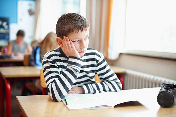 bored little school boy in classroom looking out of window - detraction stock pictures, royalty-free photos & images