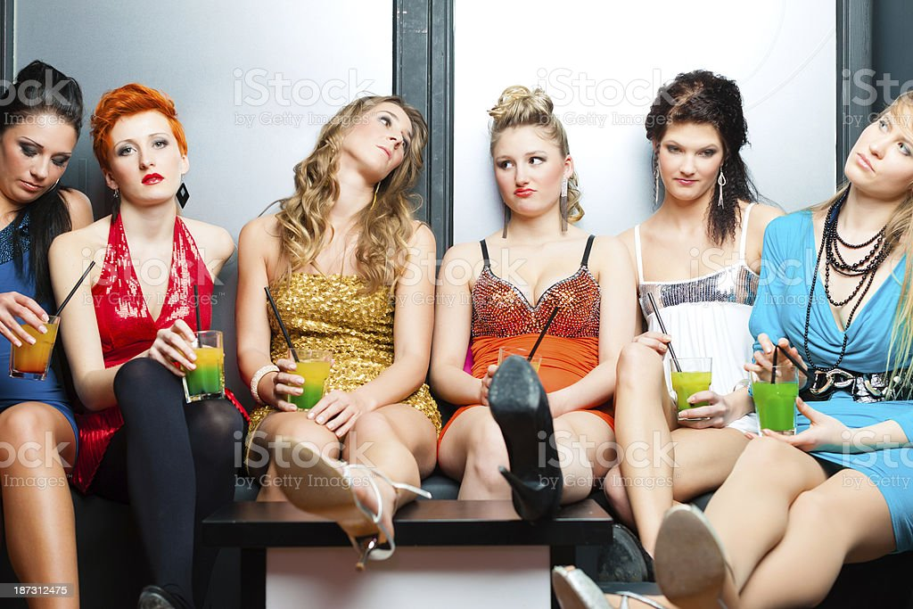 Bored looking girls at a club drinking tropical cocktails stock photo