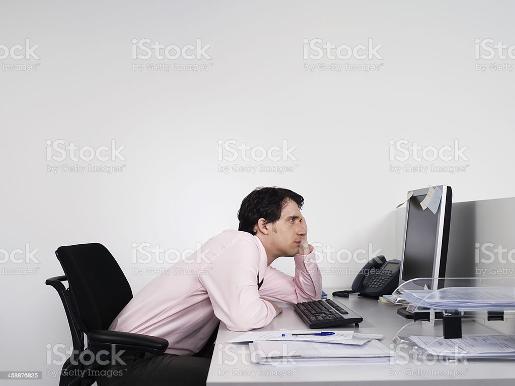 Bored Male Office Worker At Desk stock photo
