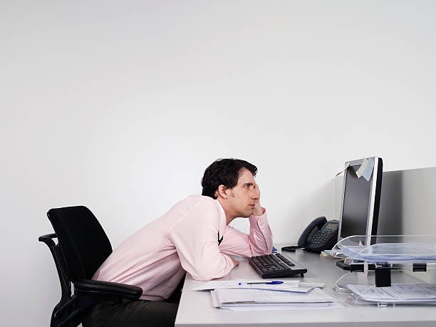 Bored Male Office Worker At Desk Side view of a bored male office worker looking at notes on computer monitor at desk bad posture stock pictures, royalty-free photos & images