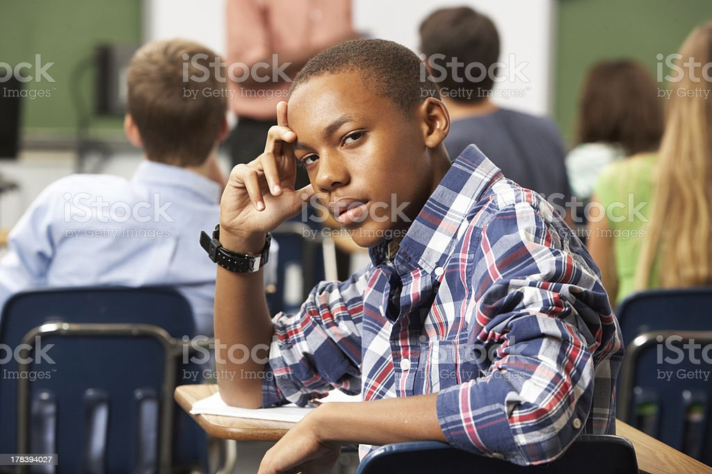 Bored Male Teenage Pupil In Classroom stock photo