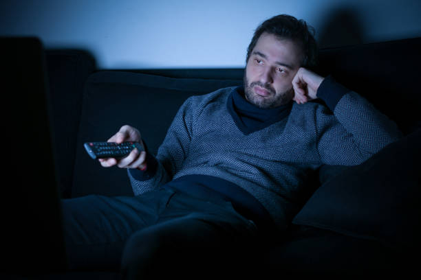 bored man watching television at night - sloth stock pictures, royalty-free photos & images