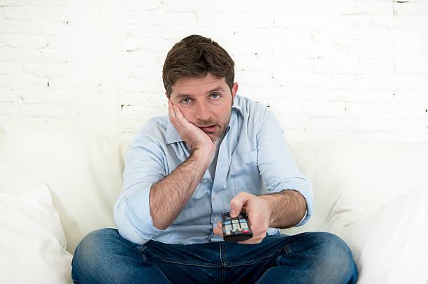 Langweilig Mann vor dem Fernseher sitzt auf Sofa halten Fernbedienung – Foto