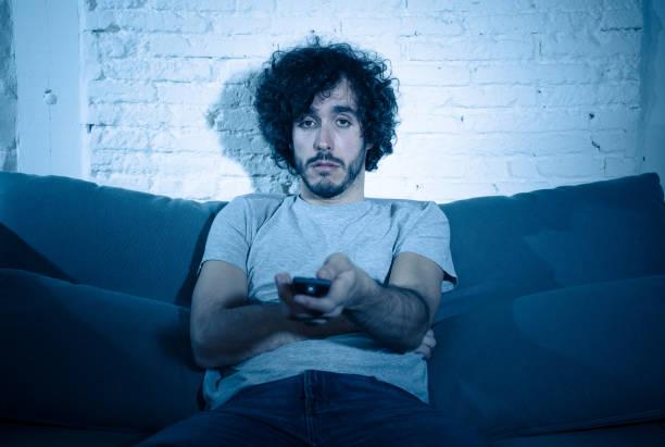 Gelangweilter Millennial-Mann, der Sitcom oder Serien beobachtet, die spät in der Nacht auf dem Sofa einschlafen. Junge männliche Zappen und wechselnde TV-Sender auf der Suche nach Show oder Film Tötung Zeit in der Nacht Gefühl unruhig – Foto