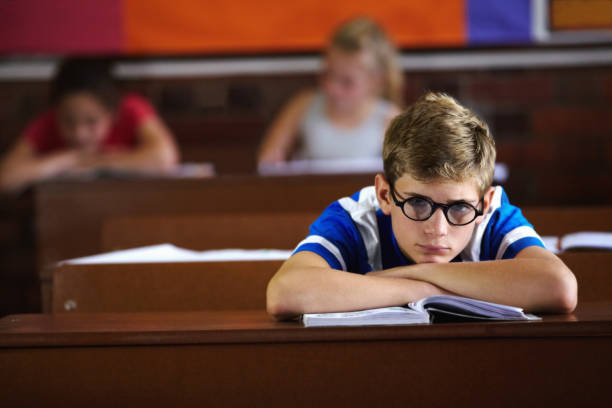 Bored of school Young boy feeling overcome with boredom in the classroom illiteracy stock pictures, royalty-free photos & images