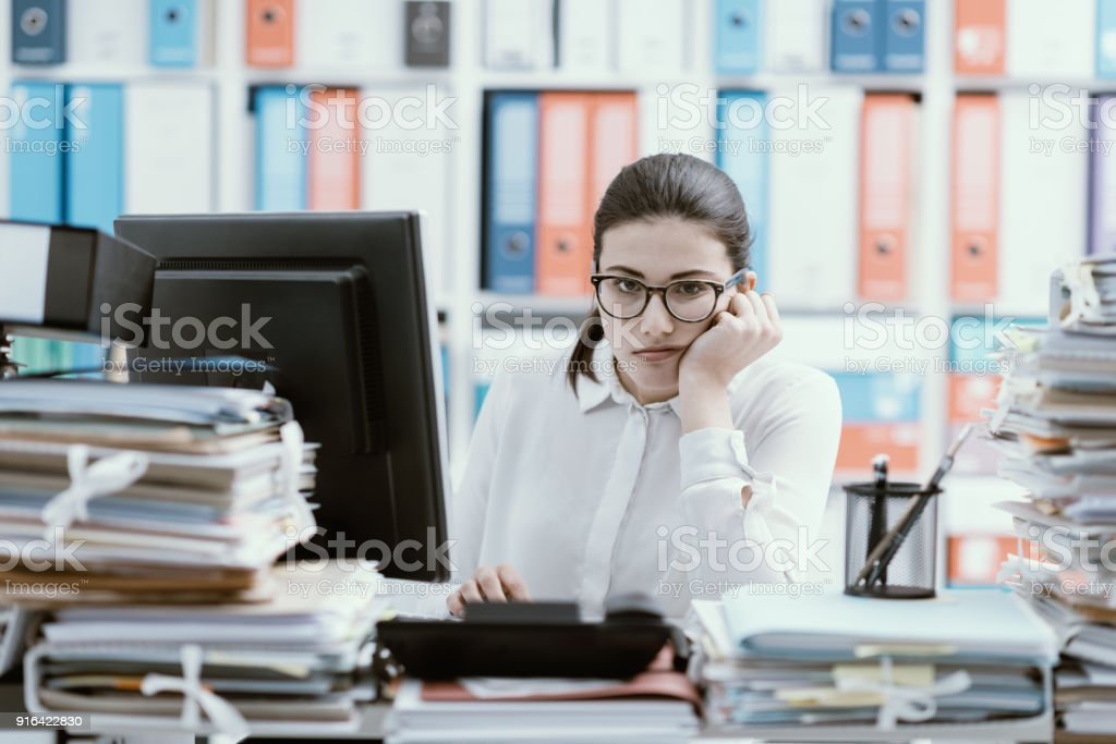 Bored office worker sitting at desk stock photo
