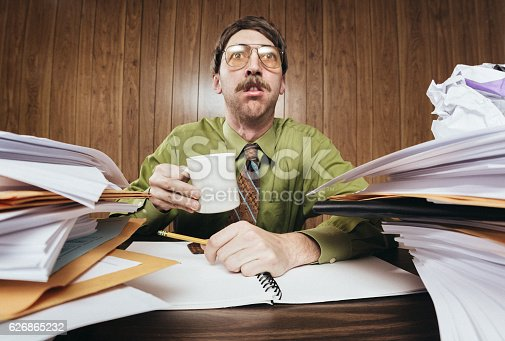 A white collar business man working in a retro 1980's style office sits at a desk piled with paperwork and documents.  He looks tired and overwhelmed at all the work he has to do.  Horizontal image.