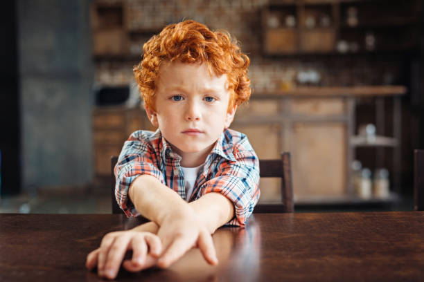 Bored redhead little boy sitting at table stock photo