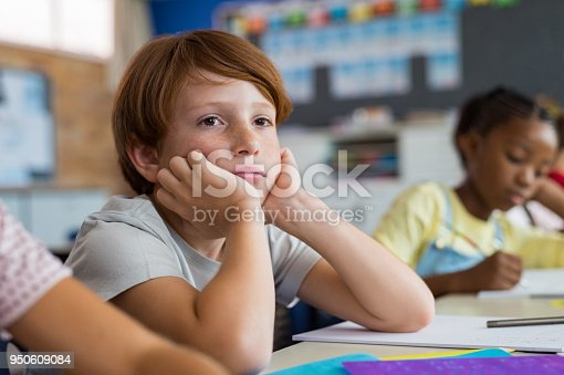 Tired school boy with hand on face sitting at desk in classroom. Bored schoolchild sitting at desk with classmates in classroom. Frustrated and thoughtful young child sitting and looking up.