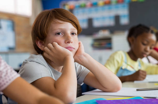 Bored school boy in class Tired school boy with hand on face sitting at desk in classroom. Bored schoolchild sitting at desk with classmates in classroom. Frustrated and thoughtful young child sitting and looking up. schoolboy stock pictures, royalty-free photos & images