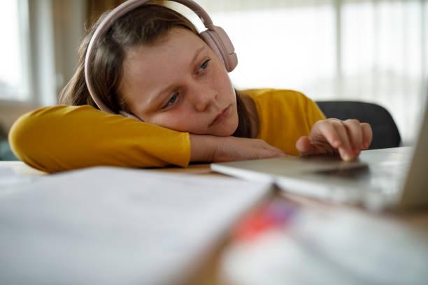 Bored school girl having online class stock photo