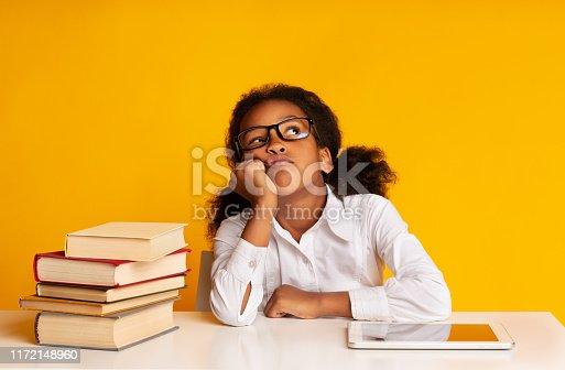istock Bored Schoolgirl Sitting Between Tablet And Book Stack In Studio 1172148960